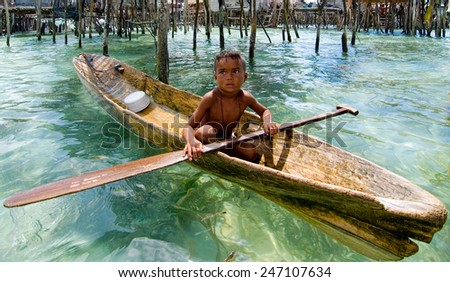 SEMPORNA, MALAYSIA - JULY 3 : Unidentified Sea Bajau's children rowing a boat July 3, 2009 in Sabah, Malaysia. Children here do not attend school for lack of means and resources. - stock photo