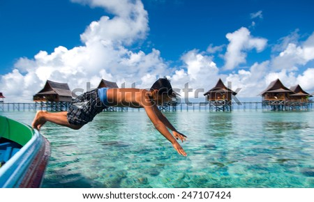 SEMPORNA, MALAYSIA - JULY 4 : Unidentified Sea Bajau's kid jump from a boat July on 4, 2009 in Sabah, Malaysia. Children here do not attend school for lack of means and resources. - stock photo