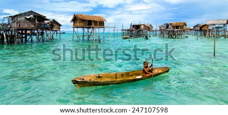 SEMPORNA, MALAYSIA - JULY 3 : Unidentified Sea Bajau's kid rowing a boat July 3, 2009 in Sabah, Malaysia. Children here do not attend school for lack of means and resources.