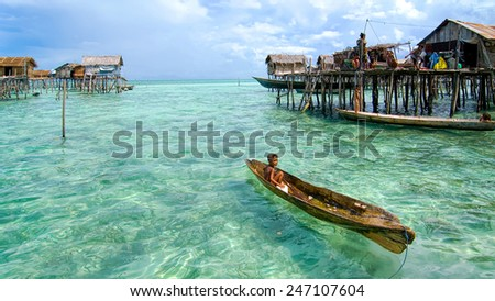 SEMPORNA, MALAYSIA - JULY 3 : Unidentified Sea Bajau's kid rowing a boat July 3, 2009 in Sabah, Malaysia. Children here do not attend school for lack of means and resources. - stock photo