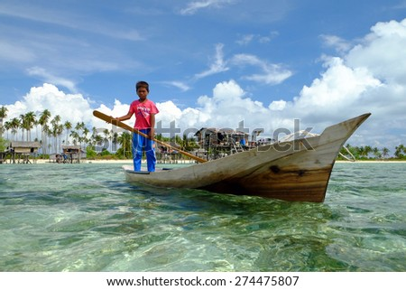 SEMPORNA, SABAH, BORNEO - APRIL 19 : Unidentified kids paddle a dug out boat on APRIL 19, 2015 in Semporna, Sabah, Malaysia. They inhabit villages built on stilts in the middle of ocean.