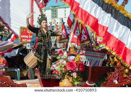 Semporna Sabah Malaysia - Apr 23, 2016 : Bajau lady dancing on traditional boat called Lepa Lepa decorated with colorfull sail known as Sambulayang during the annual Regatta Lepa Festival in Semporna.