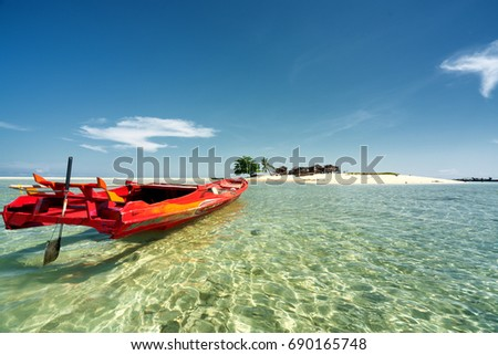 semporna, sabah, may 2017, Red boat resting in shallow water near an islan in the middle of sulu sea during midday.