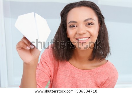 Sending message. Young beautiful smiling mulatto lady is going to throw plain made of paper. - stock photo