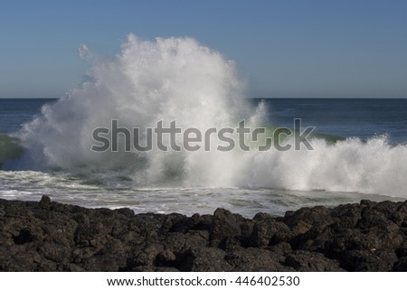 Sending salty spray high into the air spectacular backwash from the  Indian Ocean waves  are breaking on basalt rocks at  Ocean Beach Bunbury Western Australia on a sunny morning in early winter.   - stock photo