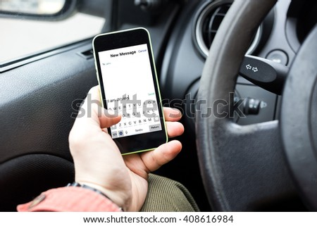 sending text from a smartphone while driving a car - stock photo