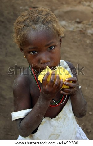 SENEGAL - FEBRUARY 15: Bedic ethnic girl posing while eating fruit, are an ethnic minority Bedic located in the country Bassari, February 15, 2007 in Kedougou, Country Bassari,Senegal - stock photo