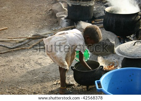 SENEGAL - FEBRUARY 15: Girl looking at food, children of ethnic Bedik assist their mothers in domestic work in the village, February 15, 2007 in Country Bassari, Senegal - stock photo