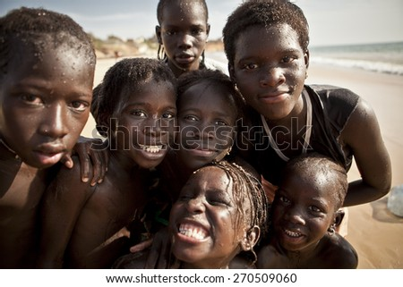 SENEGAL, Ndayane - November 9, 2013: Senegalese children on the beach of Ndayane, playing and waiting for their father to come back from fishing. Despite poverty, Senegal kids stay smiling. - stock photo