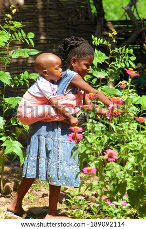 SENEGAL - SEPTEMBER 15: Girl with a baby from Dindefelo playing with flowers, September 15, 2007 in Dindefelo, Senegal - stock photo