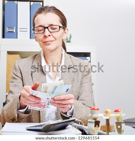 Senior accountant counting Euro money bills in her office - stock photo