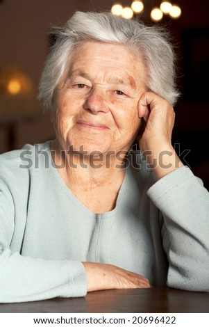 Senior adorable woman sitting at the table - stock photo