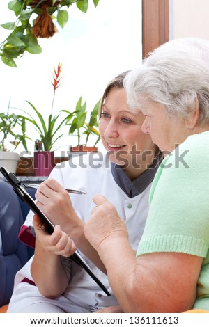 Senior adult and female nurse sit together and write data