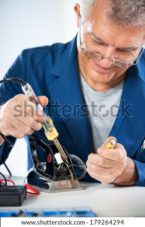 Senior adult Electrician repairing old iron with soldering iron.