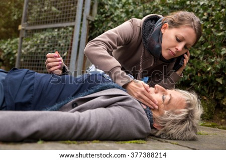 senior adult had an collapse, a young woman do first aid - stock photo