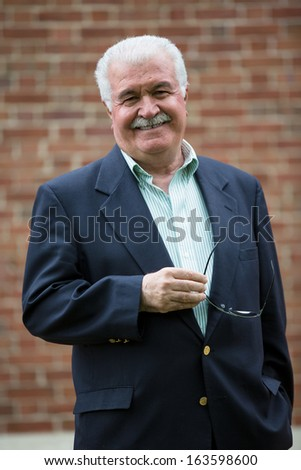 Senior adult looking at you smiling and trustfully while holding his glasses, in-front of red brick wall - stock photo