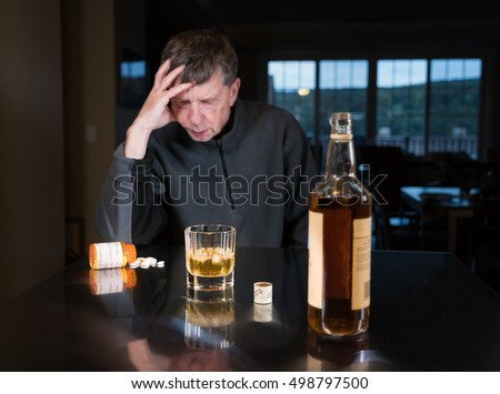 Senior adult male facing a kitchen table with alcoholic drink and looking very sad and depressed with tablets or pills