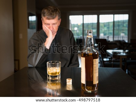 Senior adult male facing a kitchen table with alcoholic drink and looking very sad and depressed