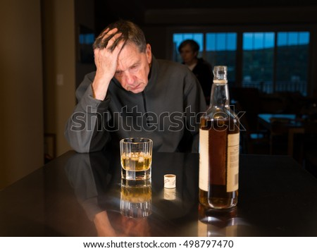 Senior adult male facing a kitchen table with alcoholic drink and looking very sad and depressed as wife is seen in the background