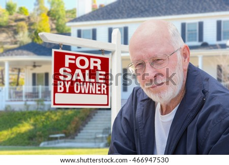 Senior Adult Man in Front of Home For Sale By Owner Real Estate Sign and Beautiful House.