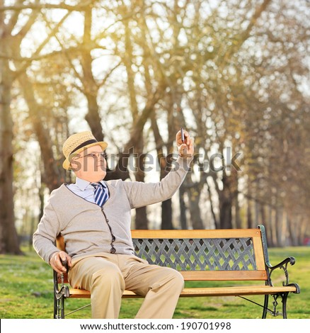 Senior adult taking a selfie in park seated on bench shot with tilt and shift lens - stock photo