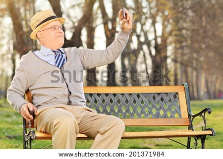 Senior adult taking a selfie in park seated on wooden bench - stock photo