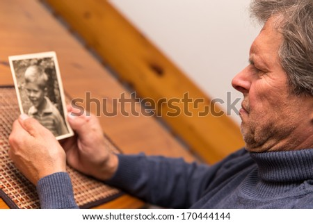 senior adult watching a photo from his childhood - stock photo