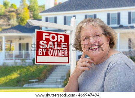 Senior Adult Woman in Front of Home For Sale By Owner Real Estate Sign and Beautiful House.