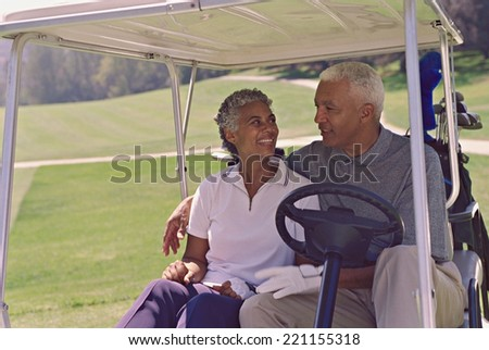 Senior African American couple in golf cart - stock photo