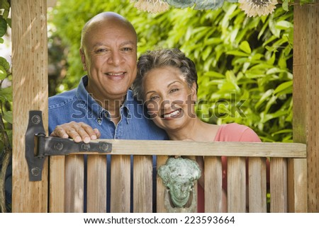 Senior African American couple looking over gate - stock photo