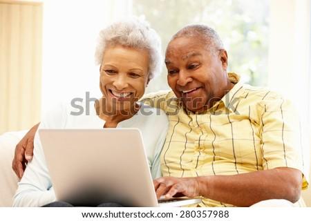 Senior African American couple using laptop - stock photo