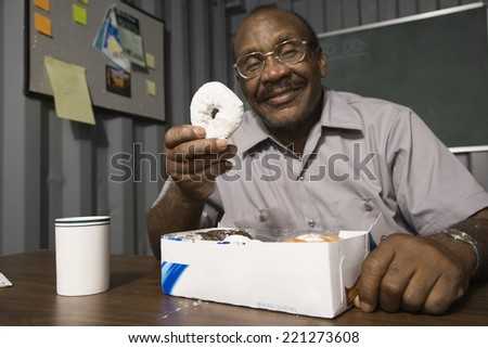 Senior African American male worker eating doughnuts