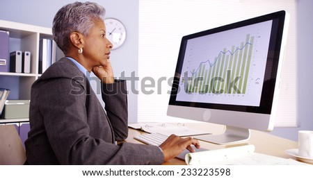 Senior African businesswoman talking on phone and working in office - stock photo