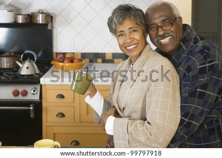 Senior African couple hugging in kitchen - stock photo