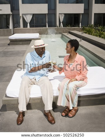 Senior African couple toasting with wine - stock photo