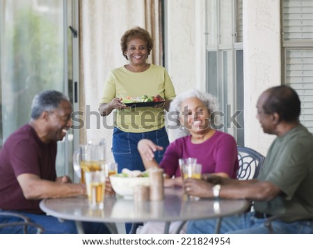Senior African couples eating on patio - stock photo