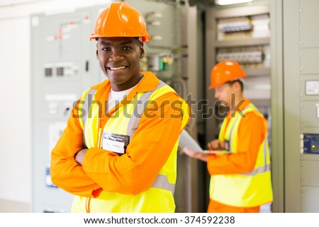 senior african industrial technician with colleague on background in control room