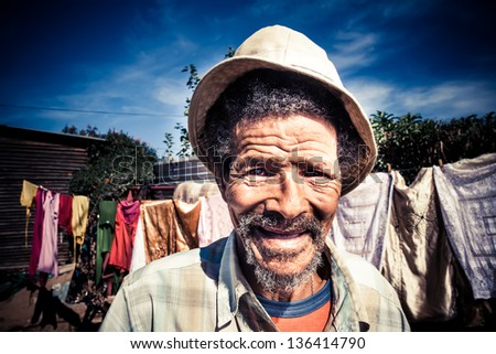 senior african man smiling brightly wearing an old khaki hat in his yard with washing in the background