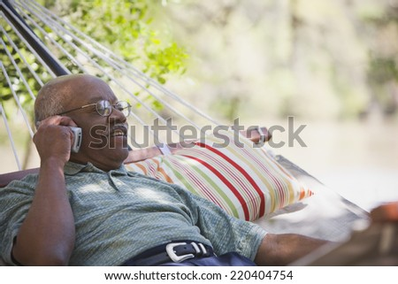 Senior African man using cell phone in hammock - stock photo