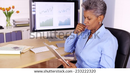 Senior african manager working at desk with tablet - stock photo