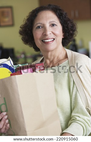 Senior African woman carrying grocery bag - stock photo