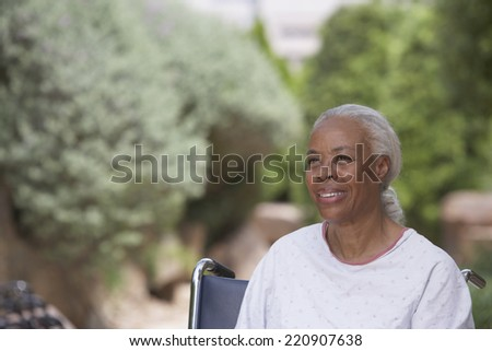 Senior African woman in hospital gown and wheelchair outdoors - stock photo