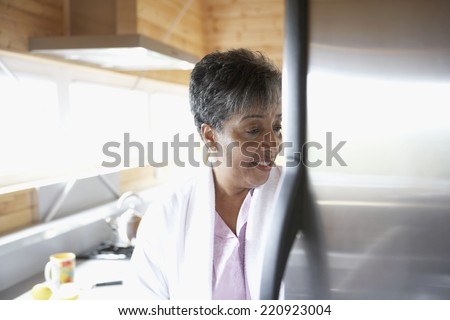 Senior African woman looking in refrigerator - stock photo