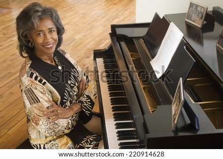 Senior African woman sitting at piano - stock photo