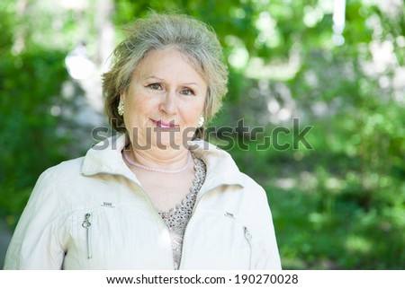 Senior aged woman outdoors in park with copy space - stock photo