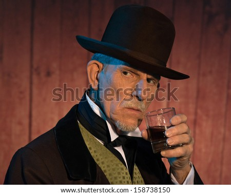 Senior alert western man wearing a brown hat and coat holding a whiskey. In front of wooden wall in saloon. - stock photo
