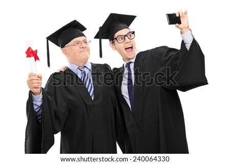 Senior and guy in graduation gowns taking a selfie isolated on white background
