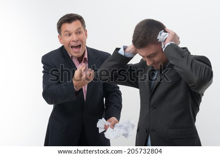 Senior and junior business people, boss angry with young handsome employee holding hands to ears with crumpled paper isolated on white