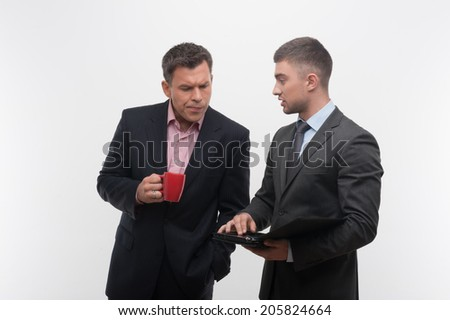 Senior and junior business people discuss something during their meeting holding coffee cup and tablet, isolated on white background - stock photo