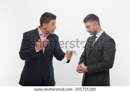 Senior and junior business people in elegant suits. Boss angry with employee looking down, holding crumpled paper isolated on white - stock photo